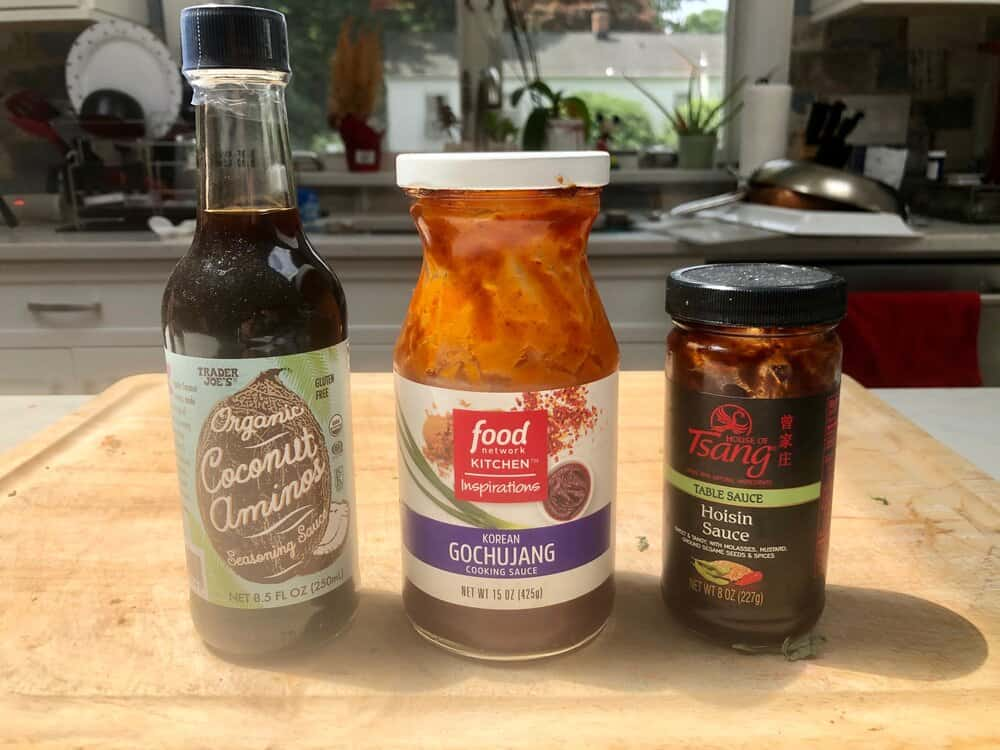 Bottles of coconut aminos, gochujang, and hoisin sauce