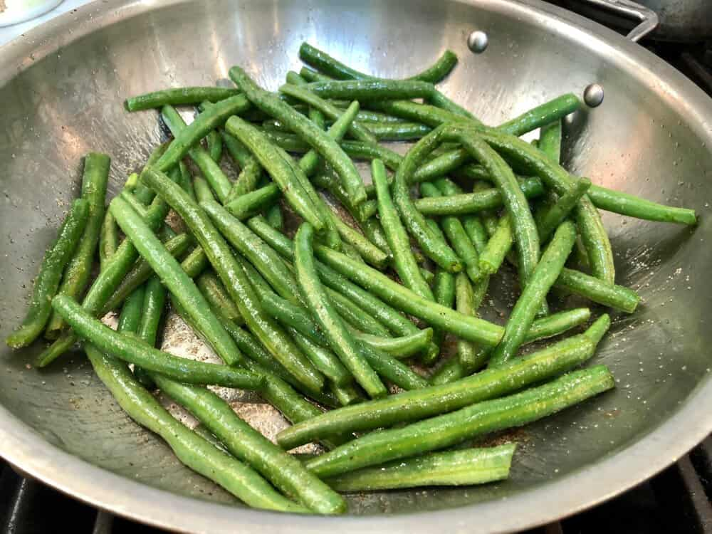 Green beans sauteeing in a pan