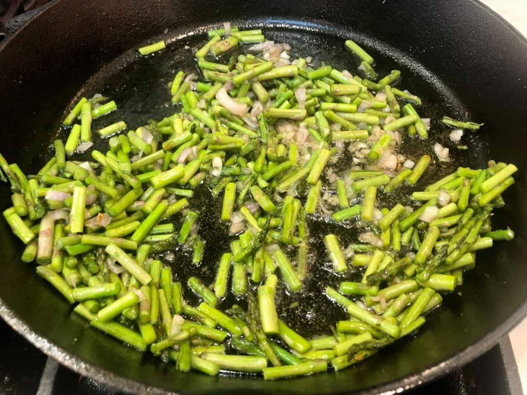 Asparagus and shallot cooking in a pan