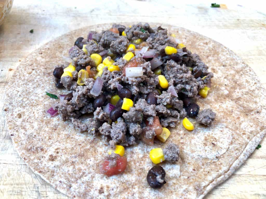 Ground beef mixture sitting on a tortilla