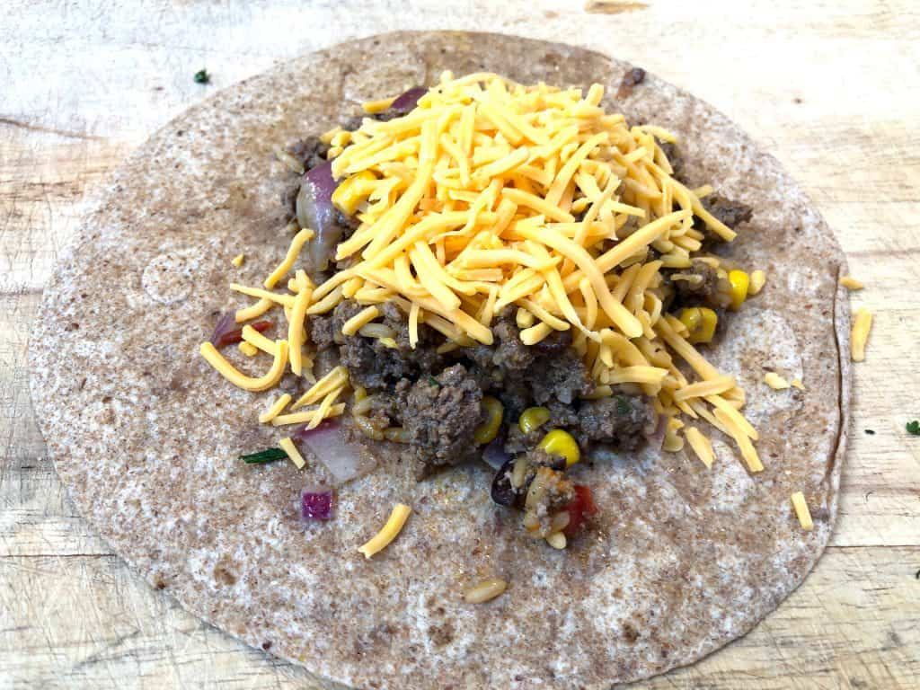 Ground beef topped with cheese on a tortilla