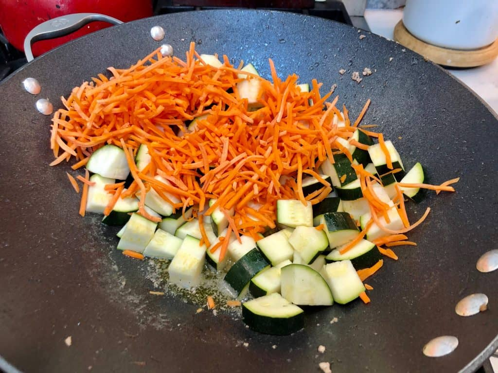 Zucchini and carrots cooking in a wok