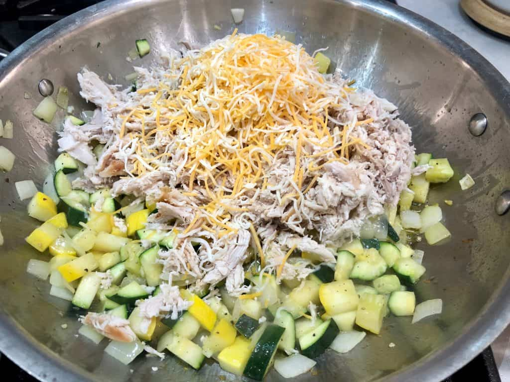 Shredded chicken, cheese and vegetables in a pan