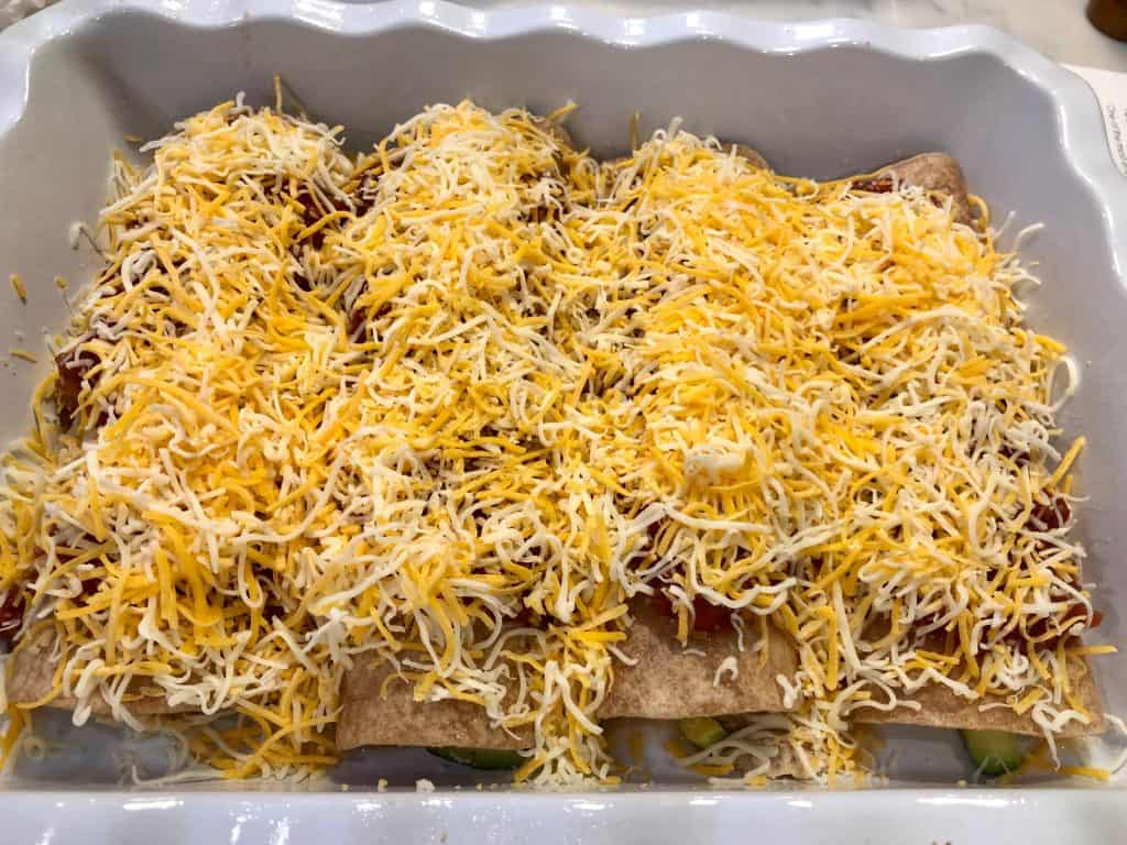 Tortillas in a baking dish topped with salsa and cheese