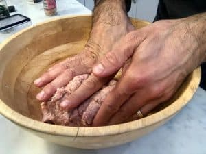 Mixing meat with hands